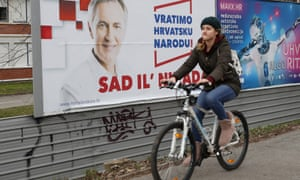 A cyclist rides past a poster of the populist presidential candidate Miroslav Škoro.