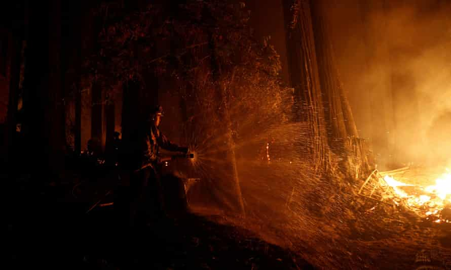 Cal Fire firefighter Anthony Quiroz defends a home in Boulder Creek, California, during the CZU Lightning Complex Fire.