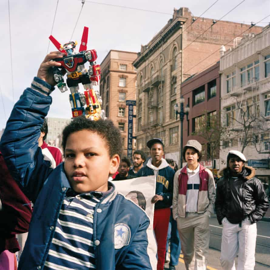 Boy With Transformer, 1986. 'This was taken at the Martin Luther King parade. That transformer is a nice metaphor for the transformation that was happening all around us. The fact that he has it on his head is so childlike – he's saying, I want to be bigger, make me bigger, transform me. And the slightly older boys in the background add a touch of menace. Having said that, there was an incredible sense of optimism and enthusiasm that day. It was a particularly powerful moment.'