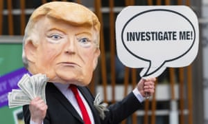 A member of the global citizens movement Avaaz wearing a mask of Donald Trump holds a sign reading 'Investigate me', outside the Scottish Parliament.