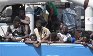 Migrants rescued in the Mediterranean Sea off Libya wait to disembark in Catania, Italy.