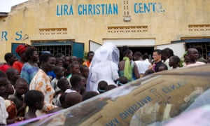 The community surrounds the bride as she enters a church in Uganda, where it is customary for men to pay a 'bride price' for their wives.