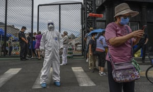 An epidemic control worker directs people at a coronavirus testing station in Beijing, China, as authorities tackle the most significant outbreak in the country since February.