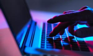 Silhouette of hand typing on laptop keyboard