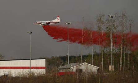 A plane drops fire retardant over an area near Fort McMurray