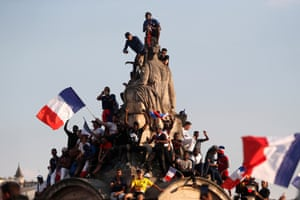 French supporters climb on a statue to greet the France's national soccer team players during a parade down the Champs-Elysee avenue in Paris