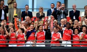 Alex Scott, Kelly Smith and Asisat Oshoala lift the trophy and celebrate their victory.