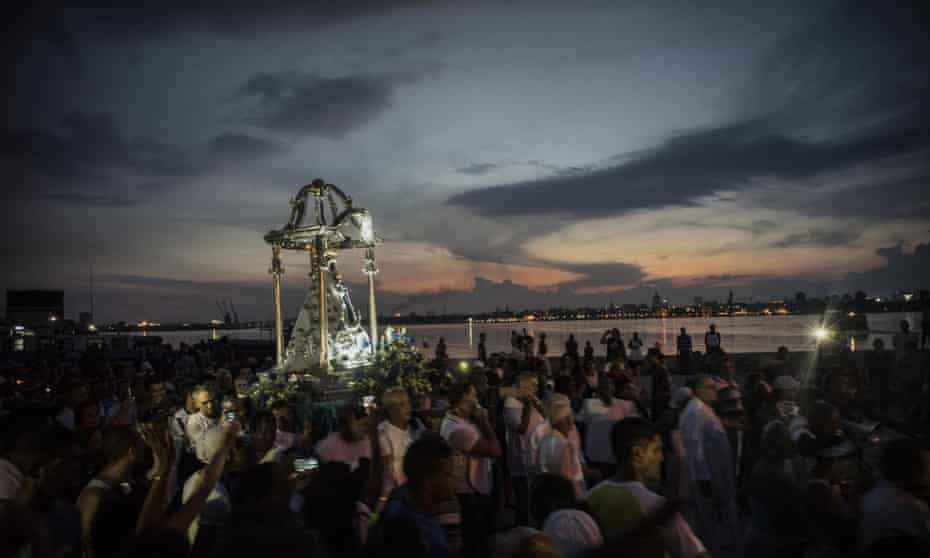 A crowd watches a procession in honor of the Virgin of Regla, in the town of Regla, across the bay from Havana, Cuba, Monday, Sept. 7, 2015. The black Madonna is honored on the same day as Cuba's patron saint, the Virgin of Charity, both of which are also recognized as powerful deities in the African-influenced religion of Santeria. (AP Photo/Ramon Espinosa)