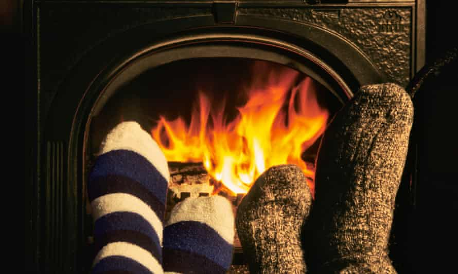 Couple warm their feet in front of an open wood burning stove.