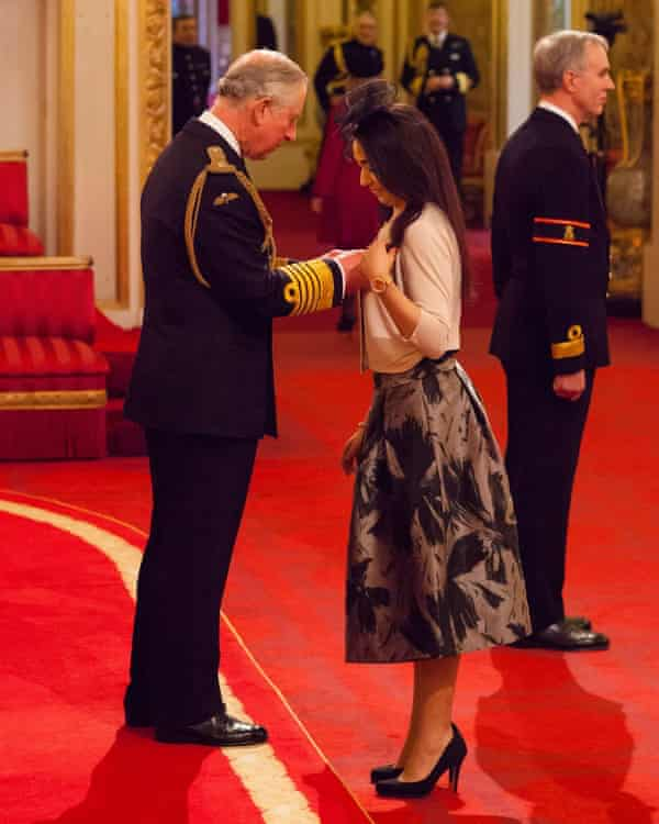 Receiving her OBE from Prince Charles.