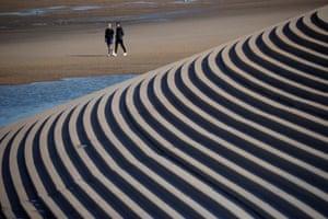 Blackpool A couple stroll along the beach