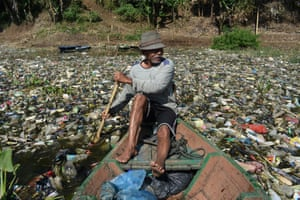 West Java, Indonesia. A man paddles his boat across the Citarum River in Bandung to collect plastic waste for recycling. The river is one of the world's most polluted, but the Indonesian government hopes to make its water drinkable again by 2025