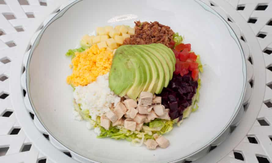 A plate with sections of chopped beetroot, tomato, minced bacon, chicken, cheese cubes, shredded egg and sliced avocado