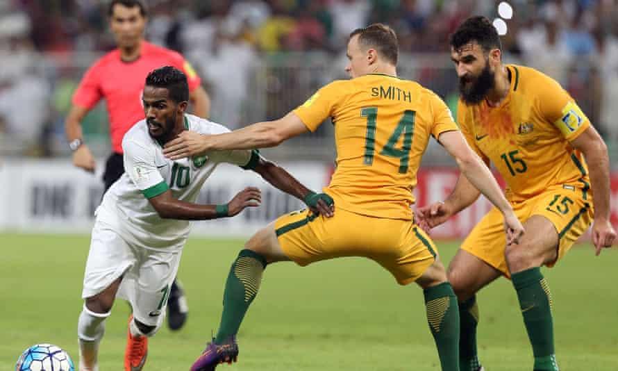 Nawaf Alabid dribbles past Australia's Brad Smith and Mile Jedinkak