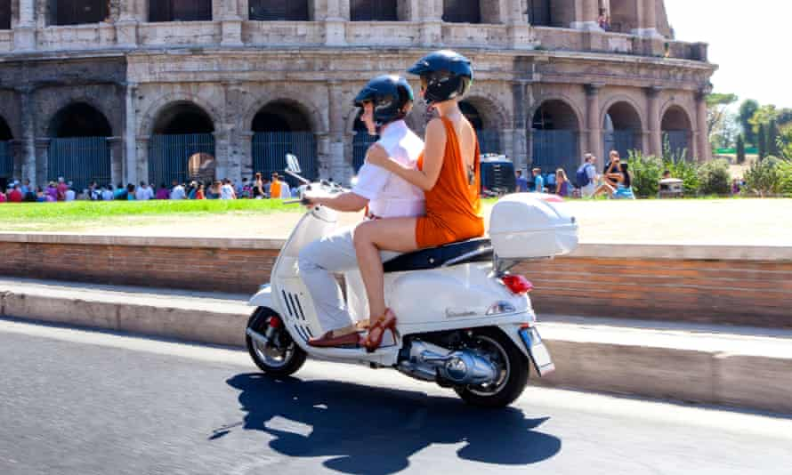 People riding a scooter past the Colosseum in Rome