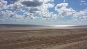 Sunny beach with flat sand and scattered clouds