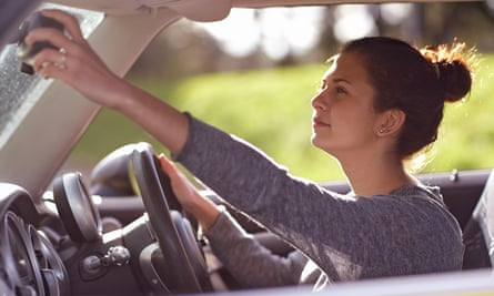 Female learner driver adjusting rear view mirror