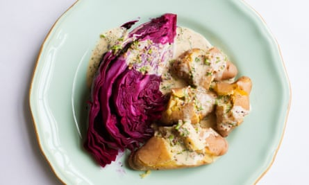 A pale green plate with a chunk of red cabbage and potatoes with a cream sauce over the top