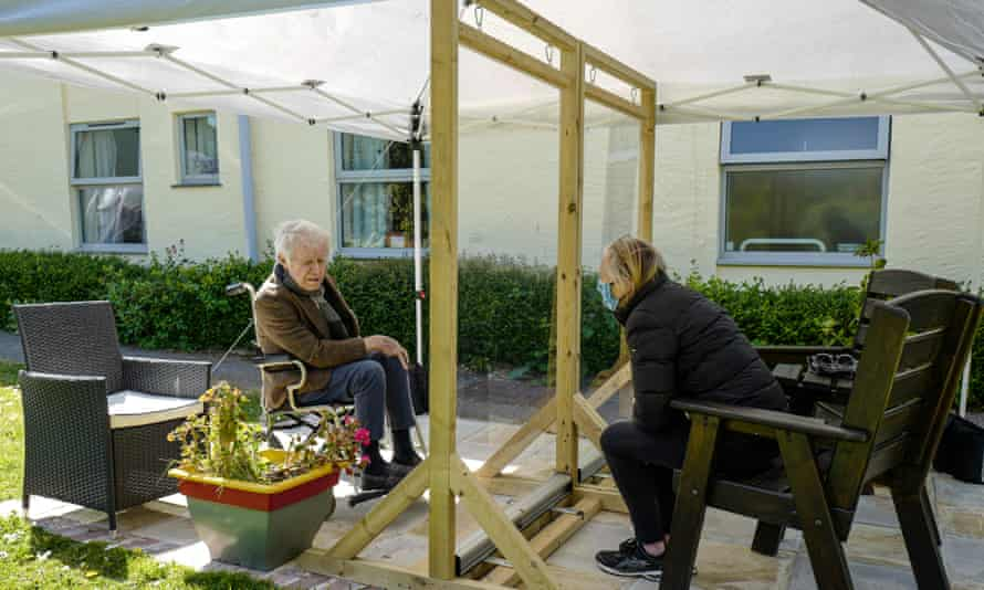 Karen Hastings visits her stepfather Gordon under an open-air shelter at the Langholme Care Home.