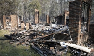 The remains of the residence at Four Paws boarding kennels smoulders along the Pacific Highway, south of Taree, on Saturday morning
