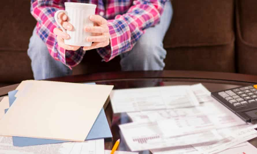 Woman sitting on sofa with large pile of invoices on coffee table in front of her.