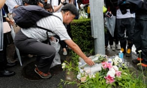 A man places flowers near the Kyoto Animation building to mourn the victims of the arson attack in Japan.
