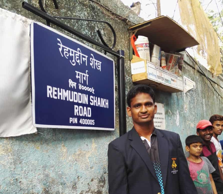 Rugby player and national women's team coach Rehmuddin Chittasahab Shaikh standing next to his street sign in Mumbai.