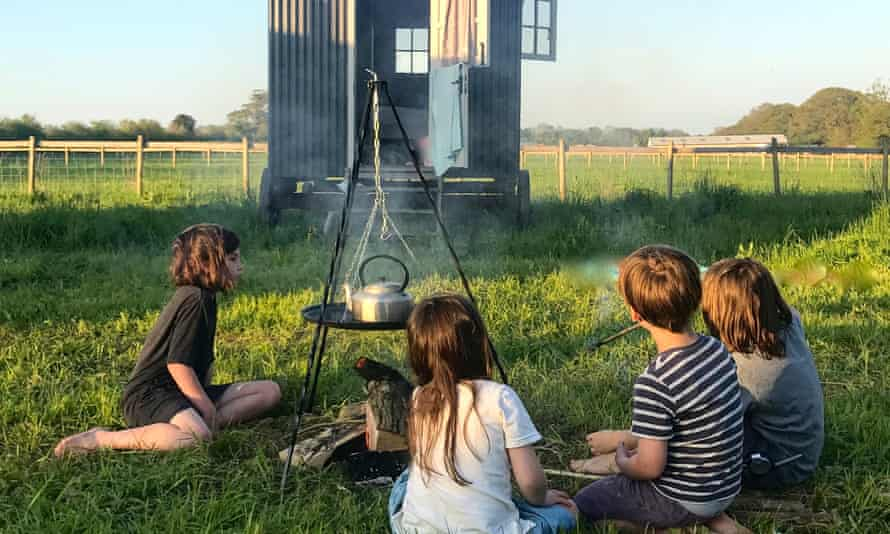 Four children around a small campfire with a kettle on a stand over it and a wooden gypsy caravan in the background