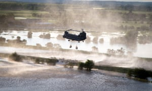 An RAF Chinook helicopter delivers gravel to try to stem the flow of water in Wainfleet, Lincolnshire.