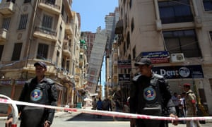 Egyptian security personnel stand guard in front of the toppled high-rise building leaning at Azarita in Alexandria.