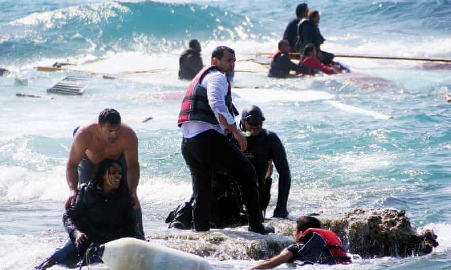 Local residents and rescue workers help a migrant woman after a boat she was travelling in sank off the island of Rhodes, Greece.