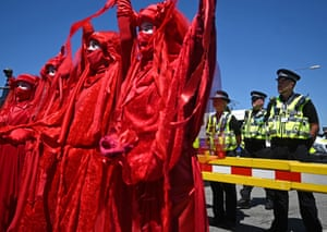 Police monitor the 'Red Brigade' group from the Extinction Rebellion environmental activists as they protest.