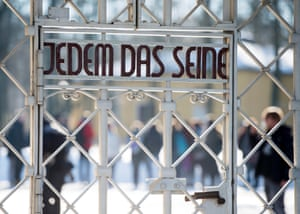 Visitors stand in front of the entrance gate of the Buchenwald concentration camp memorial
