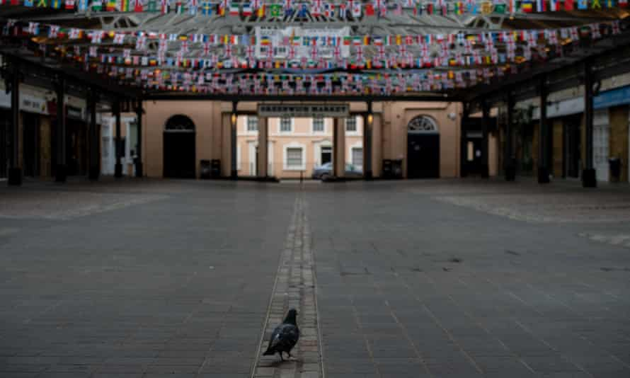 A pigeon walks through a closed and empty Greenwich Market in London on 28 April 2020.