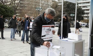 A restaurant owner throws the key of his business in a box as part of a protest over lockdown measures in Athens.