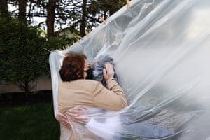 Michelle Grant (R) hugs her mother, Mary Grace Sileo through a plastic drop cloth hung up on a homemade clothes line during Memorial Day Weekend on May 24, 2020 in Wantagh, New York. It is the first time they have had physical contact of any kind since the coronavirus COVID-19 pandemic lockdown started in late February.