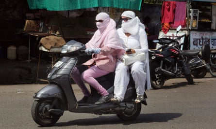 Motorcyclists are covered up to protect themselves against the scorching heat in Bhopal