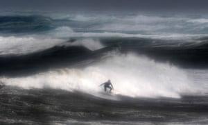 A man surfs a wave at the Pointe-de-la-Torche,Plomeur, France, as strong winds hit the coast