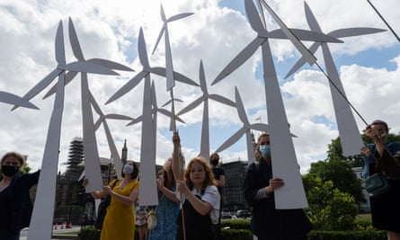 Parents and children hold handmade wind turbines, creating a wind farm, in Parliament Square before  a march to Downing Street to call for a green economic recovery.