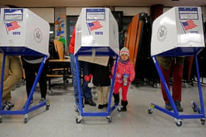 East Harlem, New York: Three-year-old Myla Gibson waits as her father, Ken Gibson, fills in a ballot at the James Weldon Johnson school
