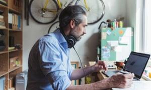 Designer with headphones working at wooden desk in home office