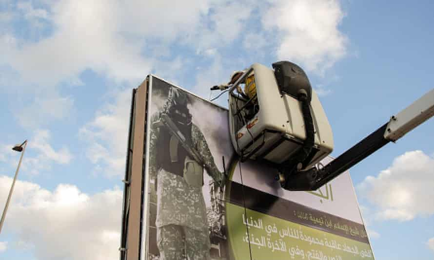 A worker is seen putting up a propaganda poster in a still from a recent Isis video