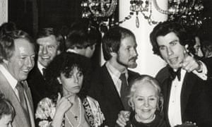 A premiere party for Saturday Night Fever withJohn Travolta, right, next to a bearded Nik Cohn, Travolta's mother below them, and producer Robert Stigwood (far left).