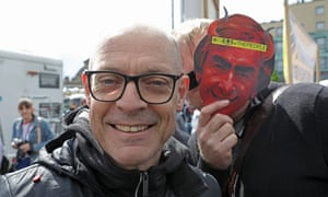Sir Dave Brailsford with a protester wearing a mask of Jim Ratcliffe with devil horns.