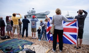 Members of the public gather to see the arrival of the vessel
