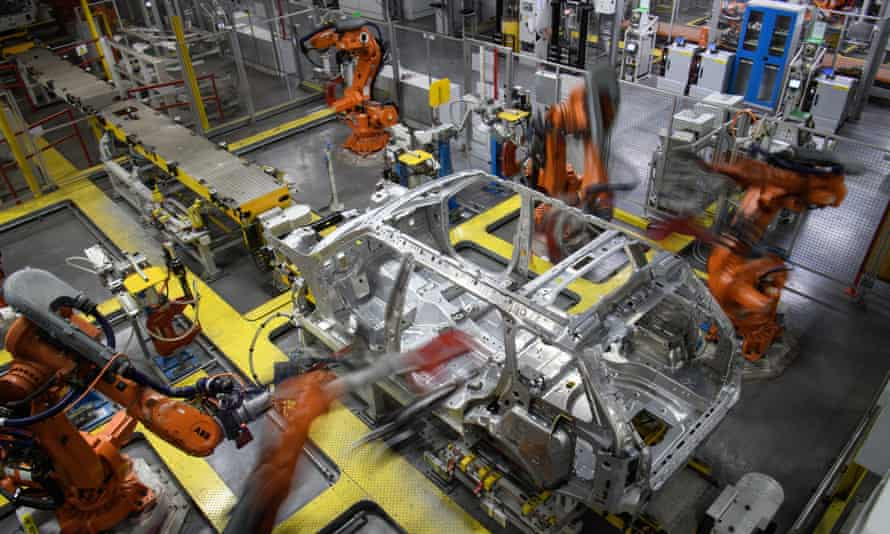 Robotic systems work on the chassis of a car during an automated stage of production at the Jaguar Land Rover factory in Solihull.