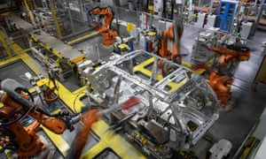 Robotic systems work on the chassis of a car during an automated stage of production at the Jaguar Land Rover factory in Solihull