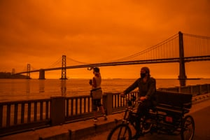 The scene from the Embarcadero looking across to the Bay Bridge to Oakland as smoke blankets San Francisco in darkness and an orange glow on Wednesday.
