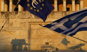 A Greek flag and a European Union flag in front of the Tomb of the Unknown Soldier monument in Athens