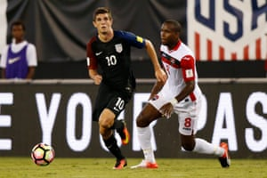 Khaleem Hyland of T&T tries to stop Christian Pulisic.